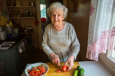 Elderly Woman Cutting Up Tomatoes